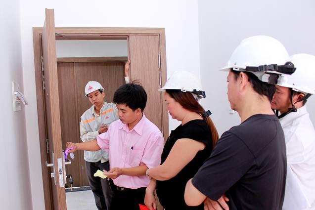 Đại diện chủ đầu tư hướng dẫn khách hàng mở cửa bằng thẻ từ khi nhận nhà.