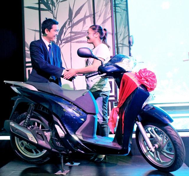 Đại diện Tập đoàn Đất Xanh (trái) trao thưởng xe Honda SH 2015 cho khách hàng Dung Thị Bích Thùy (phải)